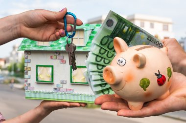 Real estate agent giving house key and model house to a new property owner, who is paying by euro money from piggy bank