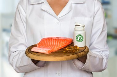Young doctor holding salmon on a wooden plate and bottle of pill with fish oil (Omega-3) and compare them