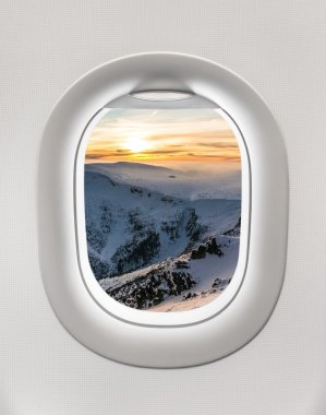 Looking out the window of a plane to the winter mountains