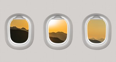 Looking out the windows of a plane to the mountains and sunset