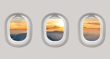 Looking out the windows of a plane to the winter mountains and s