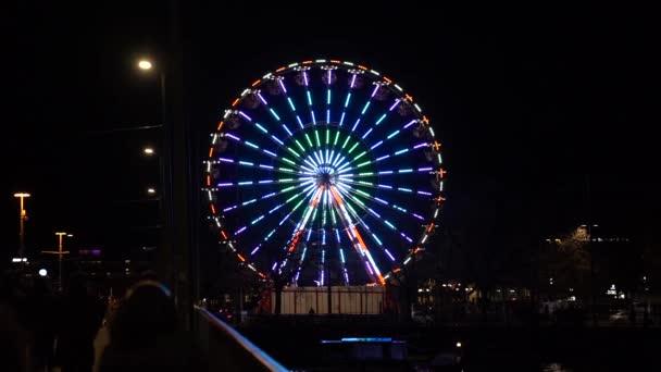 Illuminated ferris wheel in the background at city of Zurich at Friday night. Slow motion movie shot April 9th, 2021, Zurich, Switzerland.