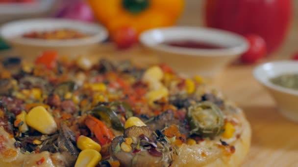 Sladké kukuřice padající na čerstvě upečenou domácí vegetariánskou pizzu - chutné jídlo. Celá pizza s chilli vločkami, rajčatovým kečupem a oreganem držená v rozmazaném pozadí