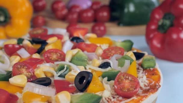Strouhaný sýr padající na lahodně pečenou domácí pizzu - italské jídlo. Extrémní detailní záběr vegetariánské pizzy s papričkami, kukuřicemi, olivami a cherry rajčaty