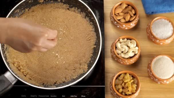 Strouhané suché ovoce a rozinky se sypou na čerstvě připravenou Sooji Halwa. Detailní záběr lahodného tradičního indického dezertu vařícího v pánvi bez lepidla - Sheera / semolina pudink