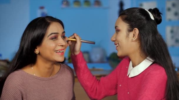 Indian girl using a makeup brush on the cheekbones of her mother - Mother Daughter Bonding. Closeup shot of teenage daughter learning to apply makeup to her mother sitting at home - cosmetics concept
