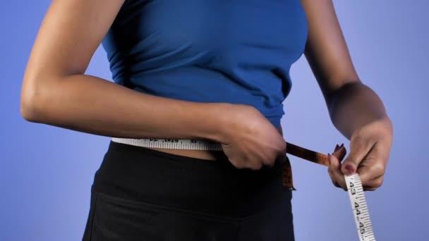 Žena si měří pas a vcucne, aby snížila čísla - úbytek hmotnosti. Detailní záběr dámského pasu měřicí páskou pro kontrolu její velikosti - aktivita, zdraví, kondice a hubnutí
