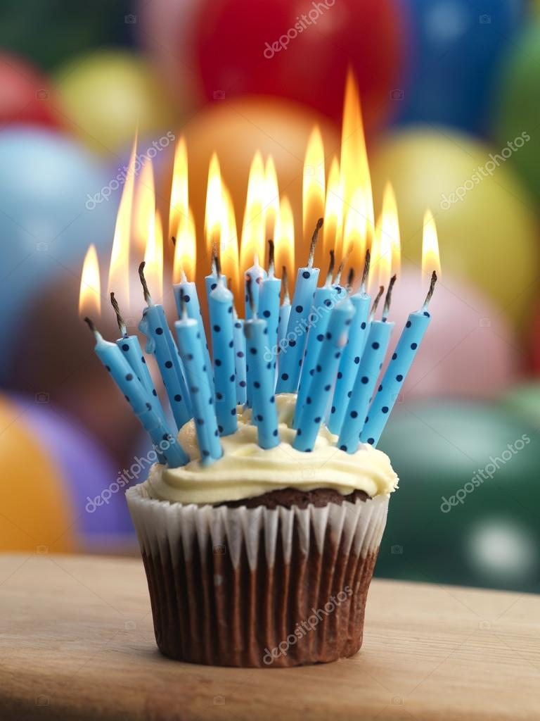 Cupcake Overflowing With Candles A Balloon Background Foto Von