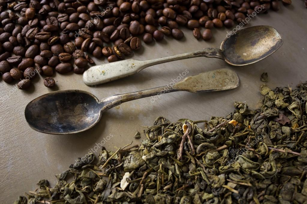 Beans of black coffee and  green tea leaves