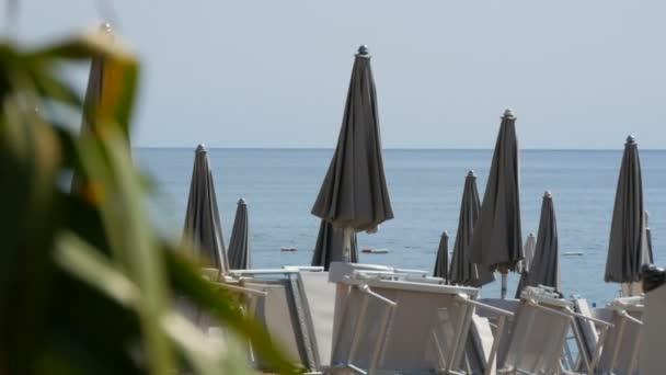 Leerer Strand an der Küste eines Badeortes, einsame Liegestühle und enge graue Sonnenschirme, abgezockter Badeort wegen Kolibris 2019, Coronavirus, Quarantäne, Adria, Montenegro