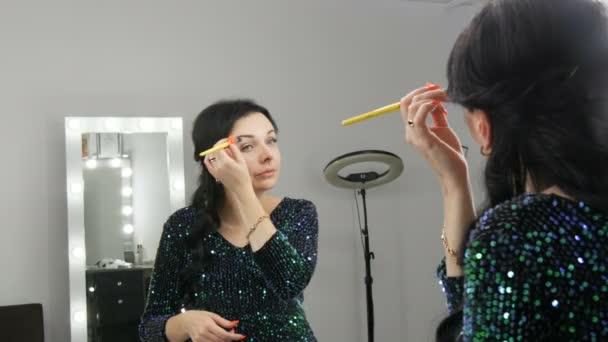 Junge schöne auffällige Frau vor dem Spiegel schminkt Gesicht und Augen mit einem speziellen Pinsel
