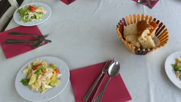 Table setting in the restaurant. Bread in a basket, vegetable salad in a plate, cutlery knife, fork, spoon on a red napkin top view