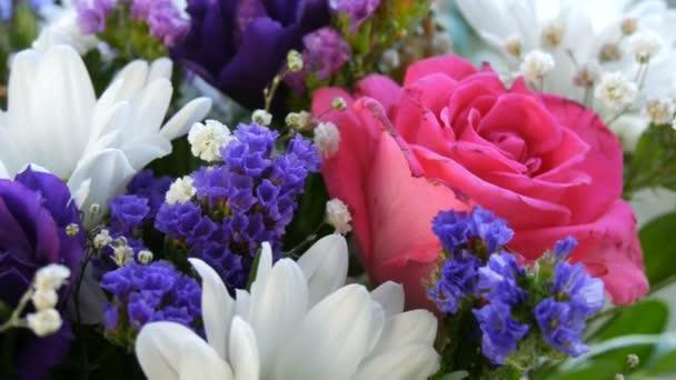 Ein schöner stilvoller Strauß aus verschiedenen bunten Blumen von Gänseblümchen, Rosen, Trockenblumen. Festlicher Brautstrauß aus weißen, rosa, blauen, lila, gelben Blumen