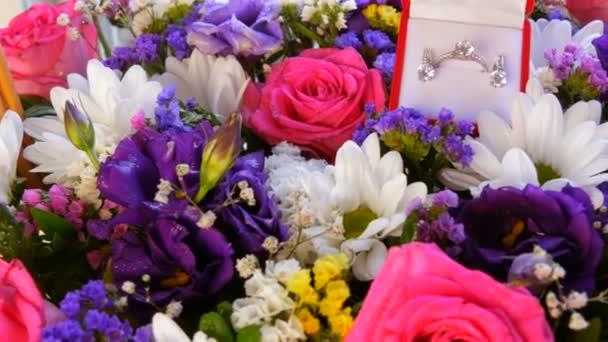 Draufsicht auf Geschenk Geschenk rote Box mit einem Satz Verlobungsring und Ohrringe auf dem Hintergrund eines bunten schönen Blumenstrauß. Heiratsantrag, ein neues glückliches Leben.