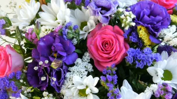 A beautiful stylish bouquet of various multi-colored flowers of daisies, roses, dried flowers. Festive bridal bouquet of white, pink, blue, purple, yellow flowers