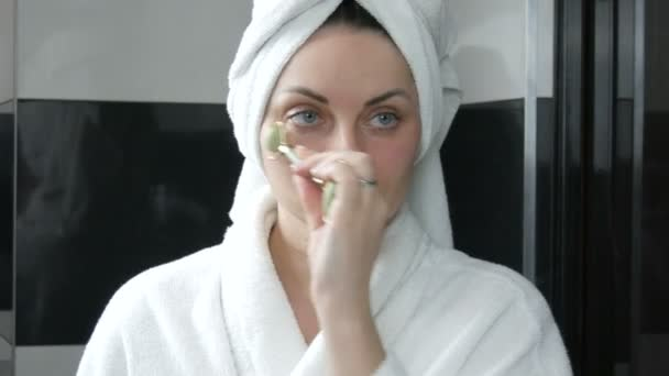 Beautiful woman with towel on head doing massage with a jade roller for the face for eye area head of stone in the bathroom. Chinese beauty tools. Lymphatic drainage skin massage against aging