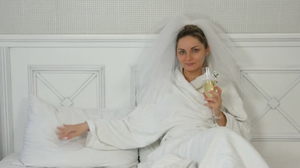 Funny young bride in a veil on the bed in the hotel drinks from wedding glasses, temptingly stroking the pillow and beckoning to her
