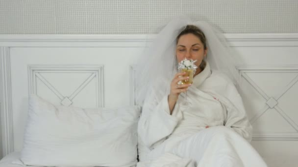 Funny young bride in a veil on a bed in a hotel drinks from wedding glasses, looking temptingly at the camera and smiling
