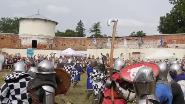 Trostyanets, Ukrajna - augusztus 21, 2021: A nézők érdeklődéssel nézik a középkori csata reprodukcióját. A lovagi páncélba öltözött emberek, a fém sisakok és pajzsok hideg acéllal harcolnak.