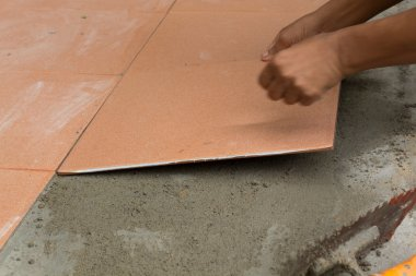 A plasterer is tiling at home, tile floor adhesive renovation at