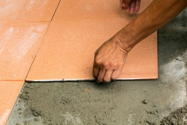 Man Construction worker is tiling at home, tile floor adhesive r