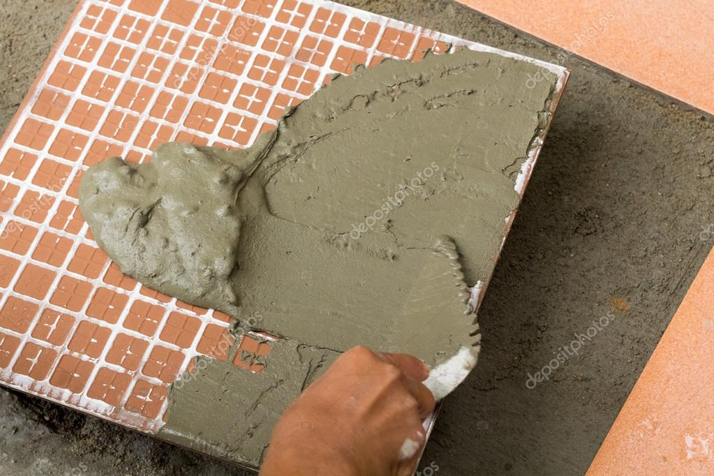 Un piastrellista sul lavoro incollaggio di piastrelle del