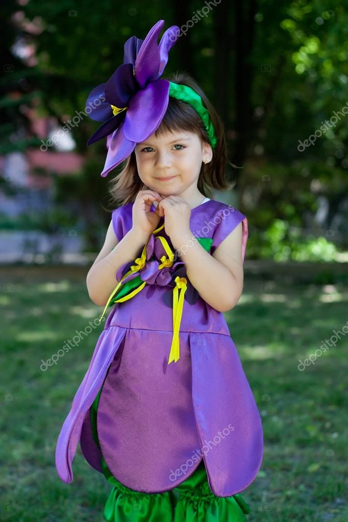 The little girl in a suit of violet flower is smiling on the bac
