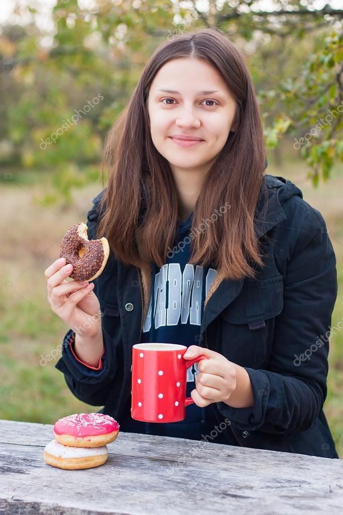Jeune fille souriante mange des beignets avec du caf sur une table en bois photographie - Vieillir du bois avec du cafe ...