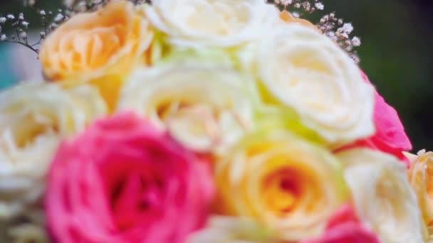 Světlé svatební kytice růží s snubní prsteny