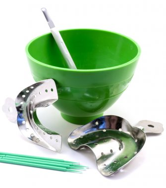 Dental metal impression trays, dental green flask, spatula, pins isolated on white