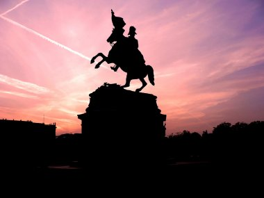 Black silhouette of monument of horse rider with flag on background of rose violet sunset