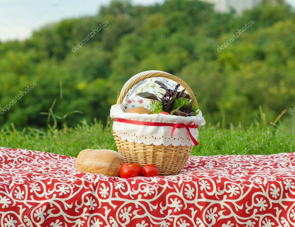 Decorated picnic basket with plate, buns and bunch of basil and salad, tomatoes on red tablecloth, green landscape