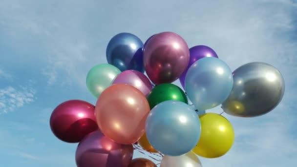 Barevné balónky s heliem pod modrou oblohou.
