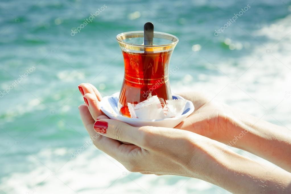 A glass of Turkish tea in the hands on the background of the Bosphorus in Istanbul, Turkey.