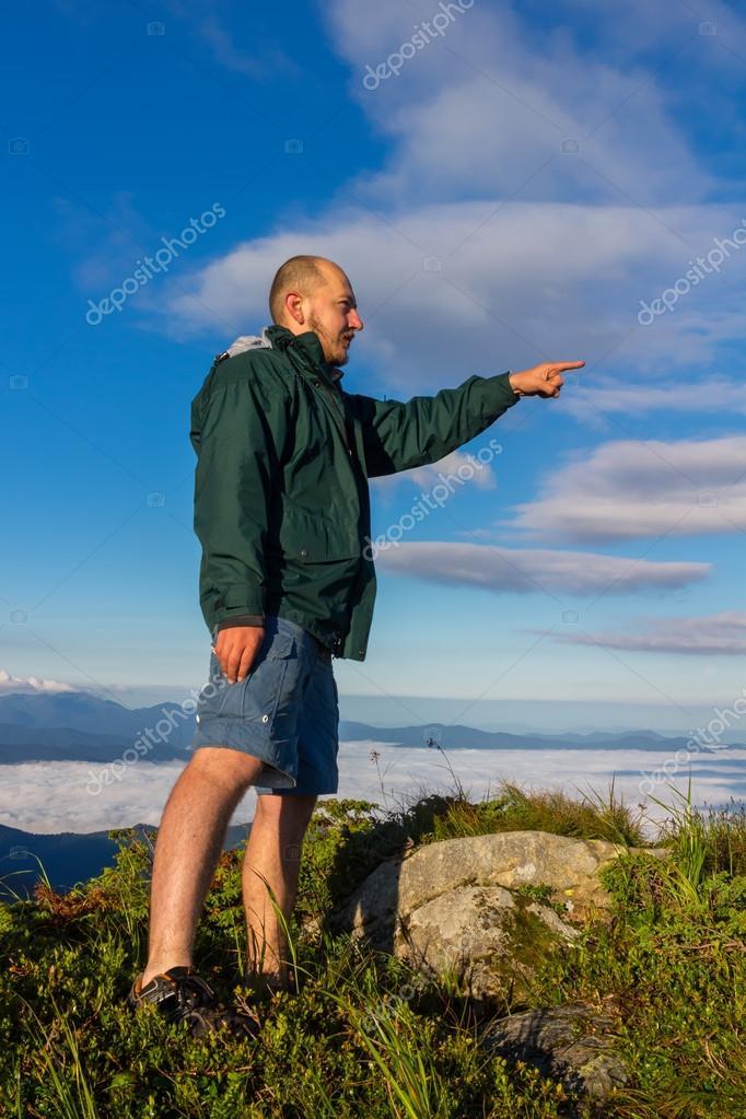 Jeune homme debout au sommet de la montagne et montre le doigt au loin dans  la durée de l aube, Carpates — Image de Farion O 85e1658dcda