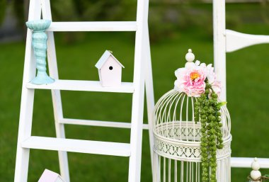 Vintage wedding decoration with white wooden wall, parrot and bird cage.