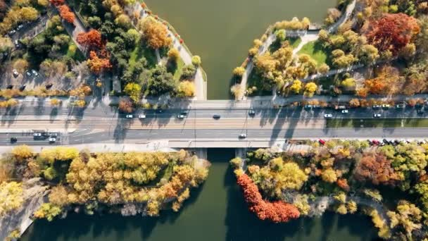 A road over the the lake with moving cars in the Titan park, multiple greenery. View from the drone, Bucharest, Romania