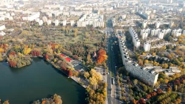 A road with moving cars an lake near the Titan park, multiple greenery and residential buildings. View from the drone, panorama view, Bucharest, Romania