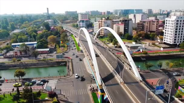 BUCHAREST, ROMANIA - OCTOBER 18, 2020: Grozavesti bridge passing over a channel, moving cars, modern commercial and residential buildings, greenery. View from the drone