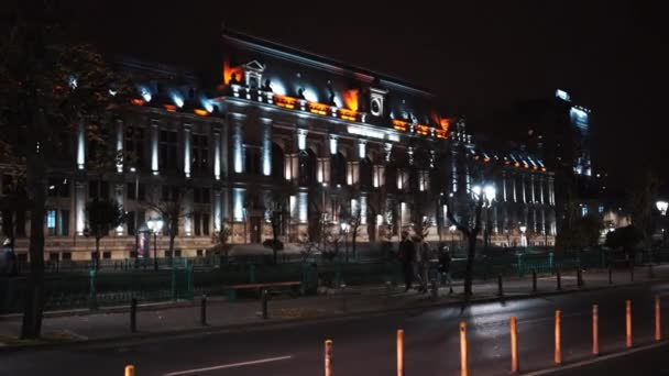 BUCHAREST, ROMANIA - NOVEMBER 21, 2020: Court of Appeal at night with street in front of it, moving car and walking people