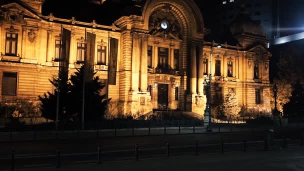 BUCHAREST, ROMANIA - NOVEMBER 21, 2020: The CEC Palace at night, yellow illumination, moving cars on the foreground