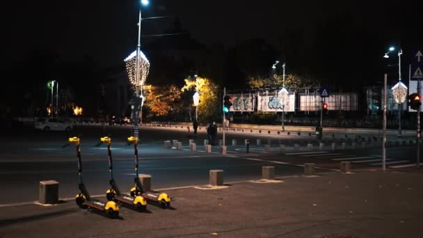 BUCHAREST, ROMANIA - NOVEMBER 21, 2020: Rows of parked electric scooters for sharing at night, walking people on the street