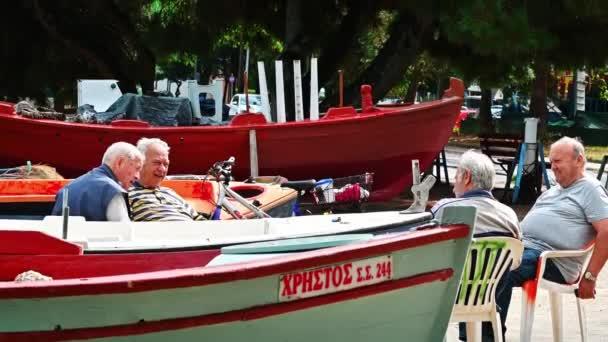 STAVROS, GÖRÖGORSZÁG - SZEPTEMBER 26, 2020: Négy öregember pihen a tengerparton strandolt csónakokkal körülvéve, utca a háttérben