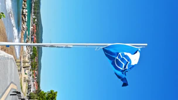 A blue flag with a sign on it near the embankment street, greenery, Aegean sea cost in Nikiti, Greece. Vertical shooting