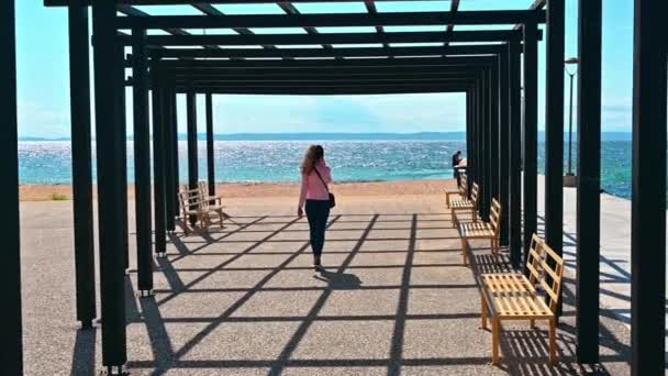 NIKITI, GREECE - OCTOBER 5, 2020: A woman talking on the phone in a gazebo on a pier with black metal posts and a benches, Aegean sea