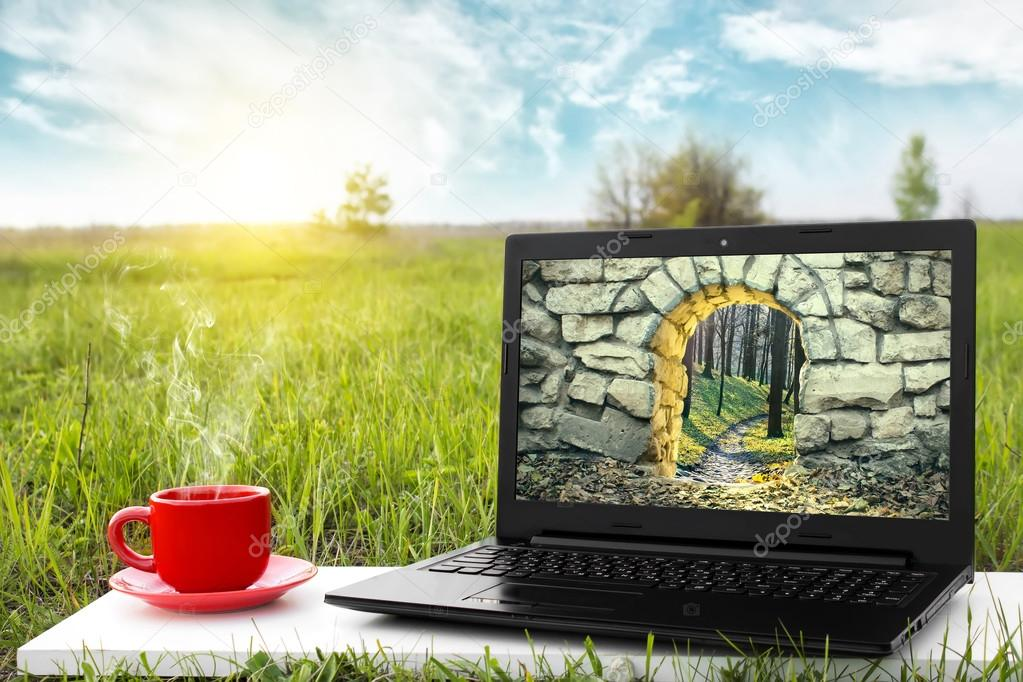 Laptop and cup of hot coffee on the background picturesque nature, outdoor office