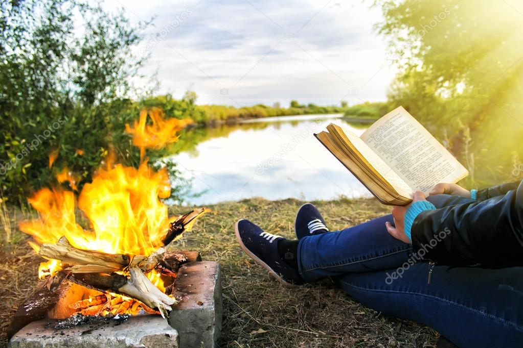 Young girl holding a up of hot coffee and reading a book near the bonfire on the background of a picturesque lake
