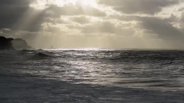 Felismerhetetlen magányos szörfös hullámok a képernyőtől jobbra és balra a viharos napfelkeltekor Bronte Beach Sydney-ben