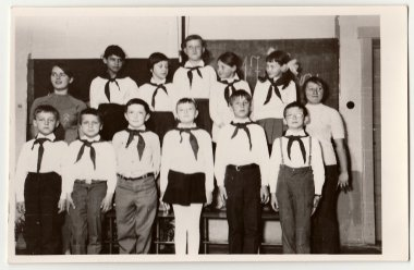 Vintage photo shows pupils with a pioneer red ties in the classroom.