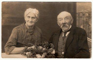 Vintage photo shows an older couple. Antique black & white photo.